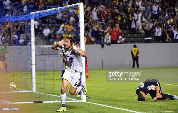 Alan Gordon of the LA Galaxy celebrates after scoring the gamewinning goal before the dejected Club America defender Paolo Goltz on July 11 2015...