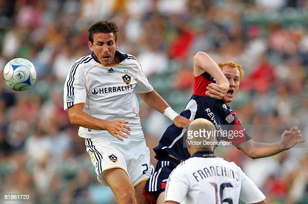 Alan Gordon of the Los Angeles Galaxy and Jeff Larentowicz of the New England Revolution vie for a high ball in the first half as Joe Franchino of...