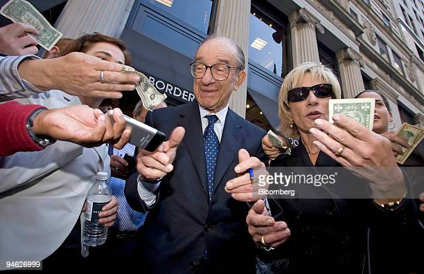 Alan Greenspan former chairman of the United States Federal Reserve Board and his wife Andrea Mitchell at right in sunglasses are surrounded by fans...