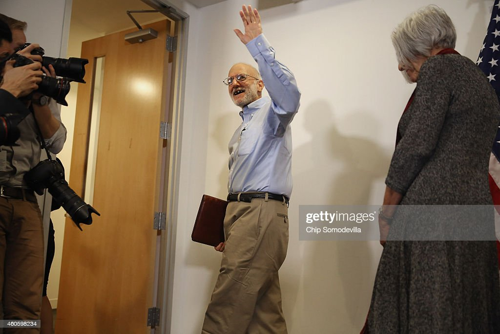 Alan Gross, with his wife Judy, waves goodbye after making a statement to the news media at the law offices of Gilbert LLC after arriving back in the United States December 17, 2014 in Washington, DC. A United States Agency for International Develpment contractor, Gross was imprisoned in Cuba for five years on espionage charges after he delivered satellite telephone equipment to Jews living on the island. Gross' release is signalling a new era in U.S.-Cuba relations as President Barack Obama announced a political thawing between the two countries, the first in more than 60 years.