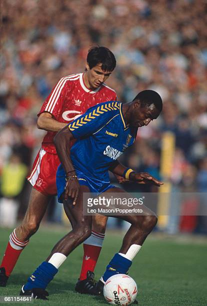 Alan Hansen of Liverpool tries to block John Fashanu of Wimbledon from advancing with the ball during a first division game between Wimbledon and...
