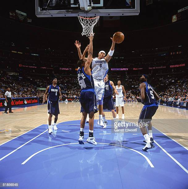 Alan Henderson of the Dallas Mavericks tries to block a shot by Kenyon Martin of the Denver Nuggets during the game at Pepsi Center on November 19...