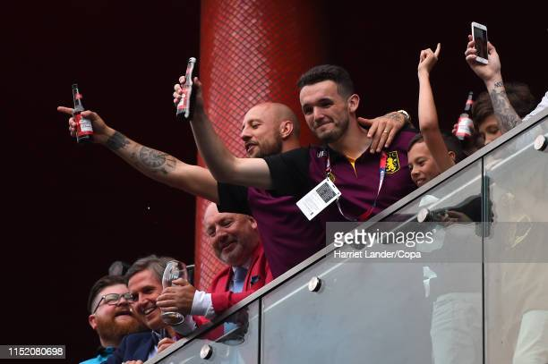 Alan Hutton of Aston Villa and John McGinn of Aston Villa celebrate on a hotel balcony with their fans in the street following their team's victory...
