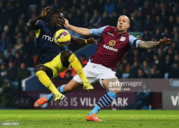 Alan Hutton of Aston Villa battles with Sadio Mane of Southampton during the Barclays Premier League match between Aston Villa and Southampton at...
