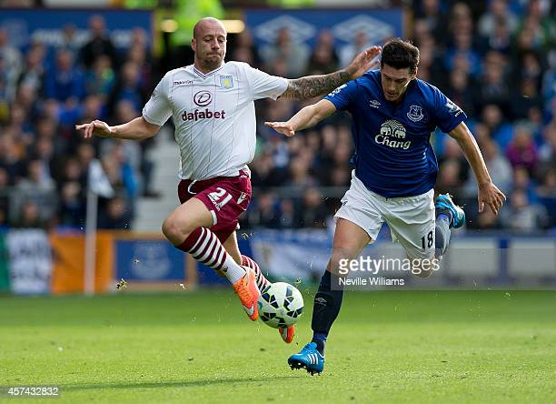 Alan Hutton of Aston Villa is challenged by Gareth Barry of Everton during the Barclays Premier League match between Everton and Aston Villa at...