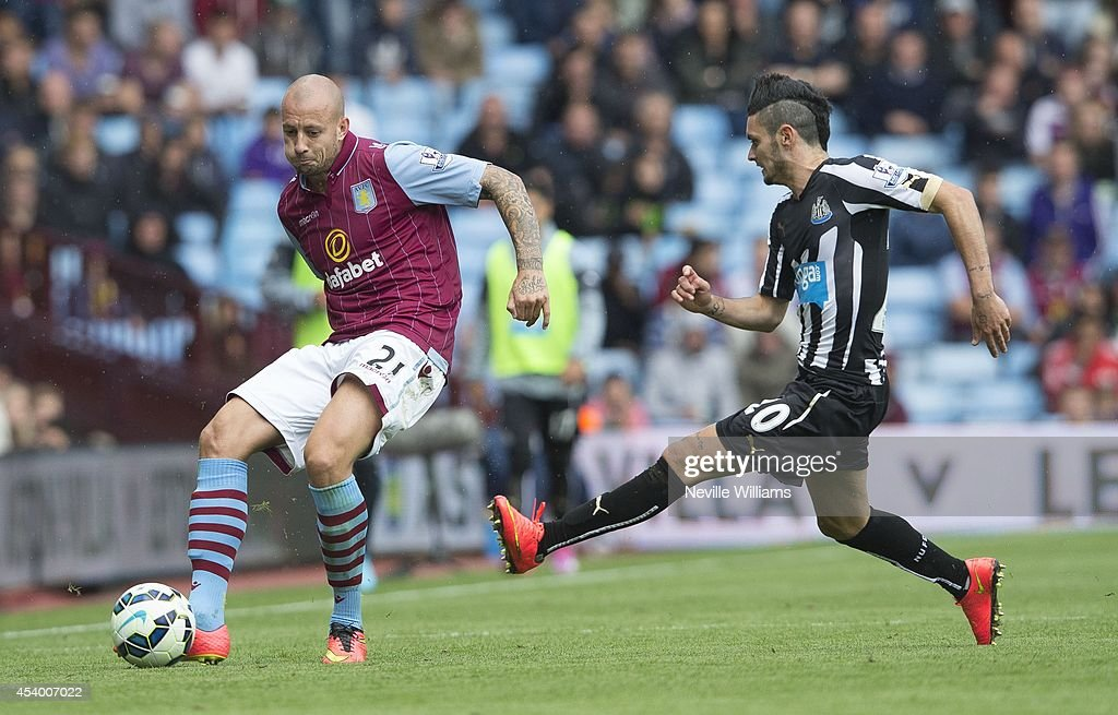 Alan Hutton (L) of Aston Villa is challenged by Remy Cabella of Newcastle United during the Barclays Premier League match between Aston Villa and Newcastle United at Villa Park on August 23, 2014 in Birmingham, England.