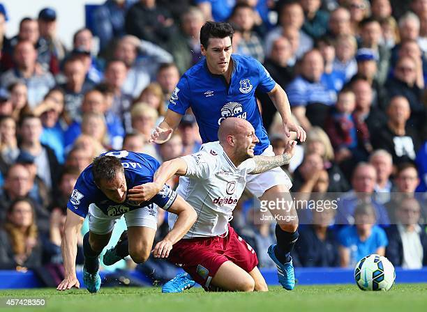 Alan Hutton of Aston Villa is closed down by Phil Jagielka and Gareth Barry of Everton during the Barclays Premier League match between Everton and...