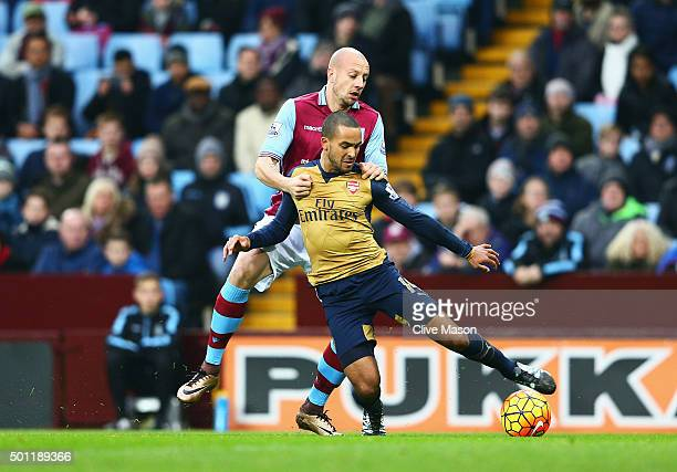 Alan Hutton of Aston Villa pulls back to Theo Walcott of Arsenal to concede a penalty during the Barclays Premier League match between Aston Villa...
