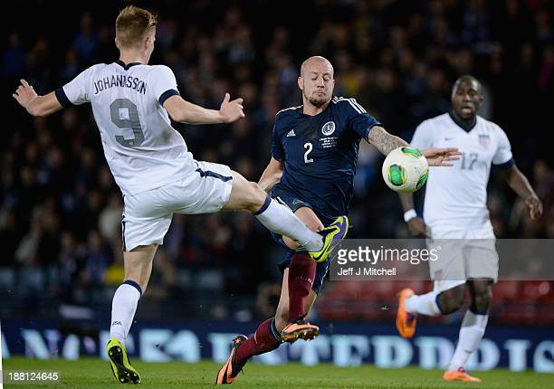Alan Hutton of Scotland tackles Aron Johansson of the USA during the international friendly at Hampden Park on November 15 2013 in Glasgow Scotland