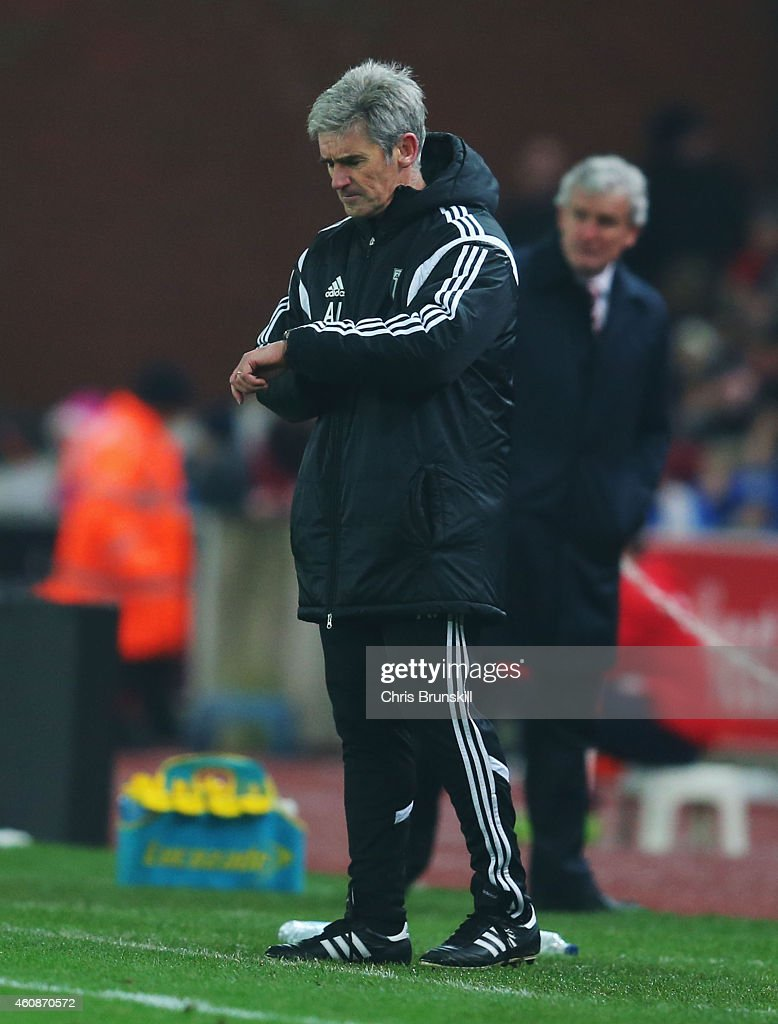 Alan Irvine manager of West Bromwich Albion checks his watch during the Barclays Premier League match between Stoke City and West Bromwich Albion at Britannia Stadium on December 28, 2014 in Stoke on Trent, England.