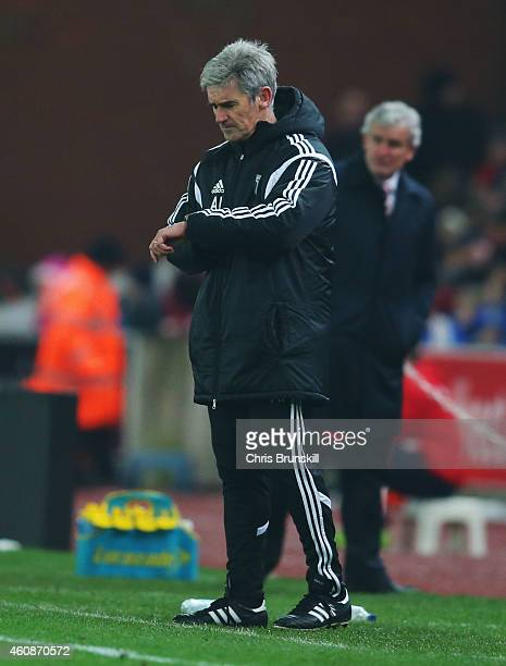 Alan Irvine manager of West Bromwich Albion checks his watch during the Barclays Premier League match between Stoke City and West Bromwich Albion at...
