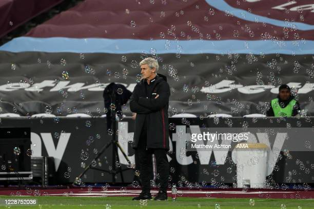 Alan Irvine the assistant head coach / manager of West Ham United looks on from the touchline as David Moyes the head coach / manager of West Ham...