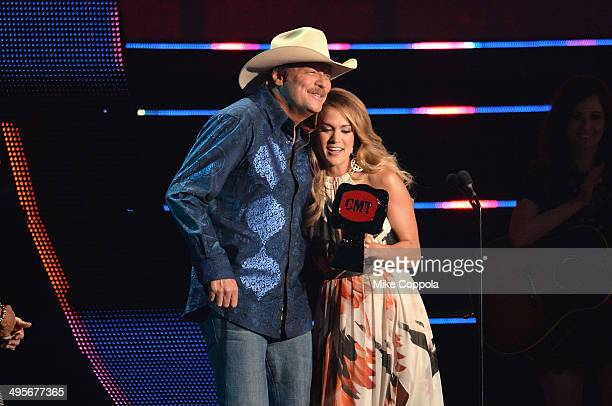 Alan Jackson accepts an award from Carrie Underwood onstage during the 2014 CMT Music awards at the Bridgestone Arena on June 4 2014 in Nashville...