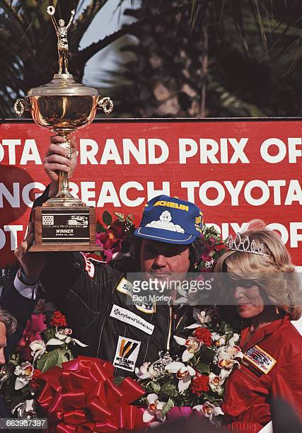Alan Jones of Australia driver of the TAG Williams Racing Team Williams FW07C Ford Cosworth DFV V8 holds the trophy aloft and celebrates winning the...