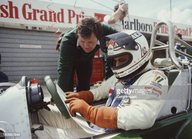 Alan Jones of Australia talks with technical director Patrick Head as he sits aboard the AlbiladWilliams Racing Team Williams FW07B Ford V8 during...