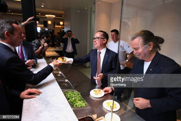 Alan Joyce chief executive officer of Qantas Airways Ltd center and chef Neil Perry right serve food to attendees during a media event ahead of the...
