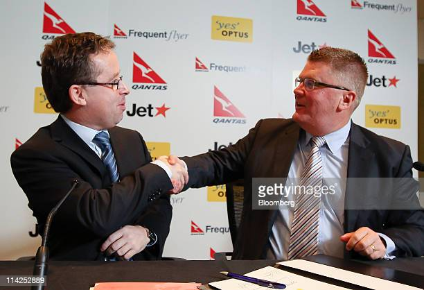 Alan Joyce chief executive officer of Qantas Airways Ltd left shakes hands with Michael Smith managing director of the consumer division of Singapore...