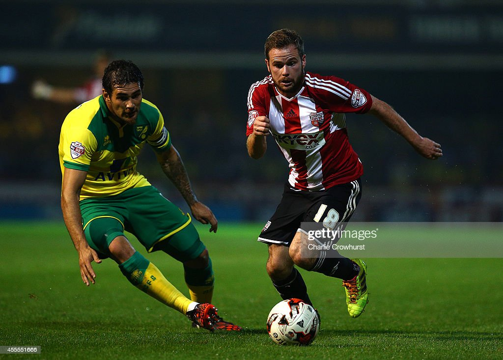Alan Judge of Brentford (R) gets past Bradley Johnson of Norwich during the Sky Bet Championship match between Brentford and Norwich City at Griffin Park on September 16, 2014 in Brentford, England.