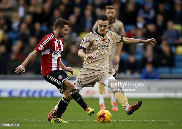 Alan Judge of Brentford passes the ball under pressure from Shaun Williams of Millwall during the Sky Bet Championship match between Millwall and...