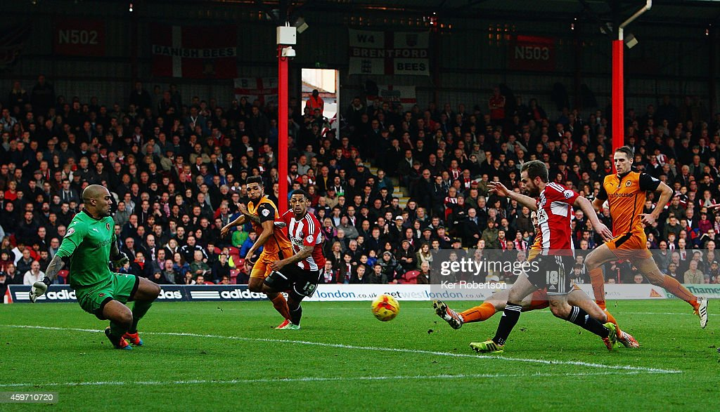 Alan Judge (#18) of Brentford shoots and scores past Carl Ikem the Wolverhampton Wanderers goalkeeper during the Sky Bet Championship match between Brentford and Wolverhampton Wanderers at Griffin Park on November 29, 2014 in Brentford, England.