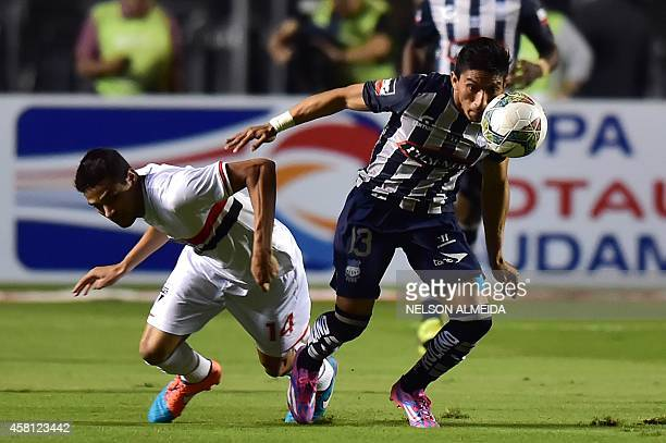 Alan Kardec of Brazils Sao Paulo vies for the ball with Angel Mena of Ecuador's Emelec during their Copa Sudamericana football match held at Morumbi...