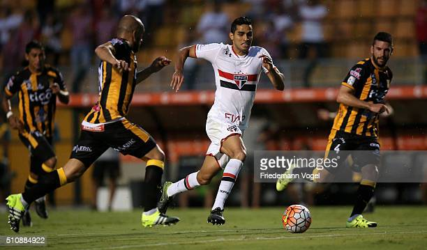 Alan Kardec of Sao Paulo fights for the ball with Ernesto Cristaldo of The Strongest during a match between Sao Paulo v The Strongest as part of...