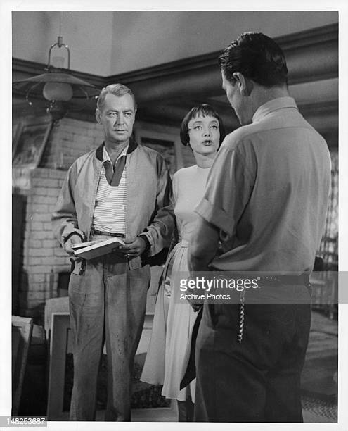 Alan Ladd and Carolyn Jones talking to man in a scene from the film 'The Man In The Net' 1959