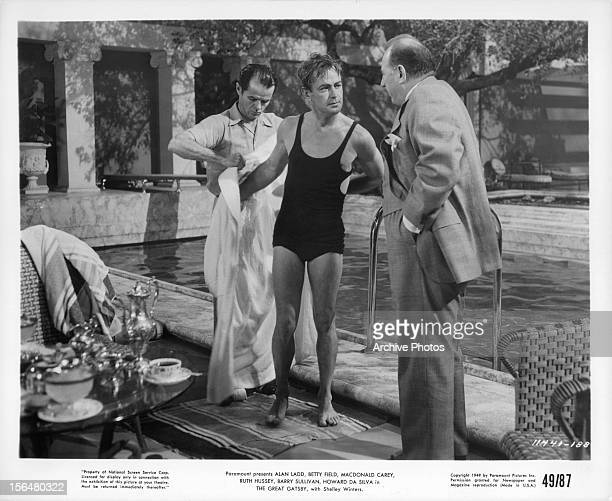 Alan Ladd is approached after getting out of pool in a scene from the film 'The Great Gatsby', 1949. Actor Elisha Cook, Jr. Holds his robe.