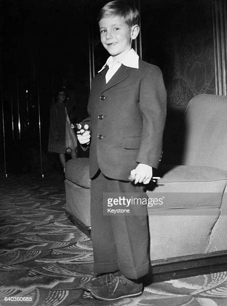 Alan Ladd Jr the son of American actor Alan Ladd poses with a toy gun at the premiere of his father's film 'Shane' at the Paramount Theatre in Paris...