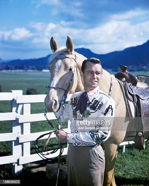 Alan Ladd , US actor, leading horse in a publicity portrait, wearing a Western shirt, circa 1955.
