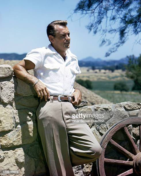 Alan Ladd US actor leaning against a stone wall in a publicity portrait wearing a white shortsleeved shirt and beige trousers circa 1955