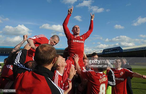 Alan McCormack of Swindon is lifted up as they celebrate their promotion during the npower League 2 match between Gillingham and Swindon Town at...