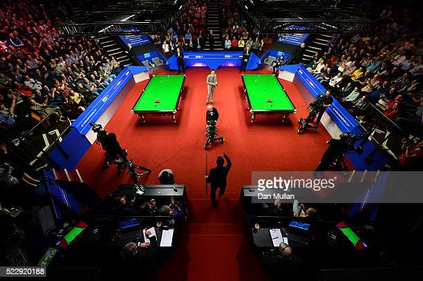 Alan McManus of Scotland makes his way into the arena for his second round match against Ali Carter of England on day six of the World Snooker...