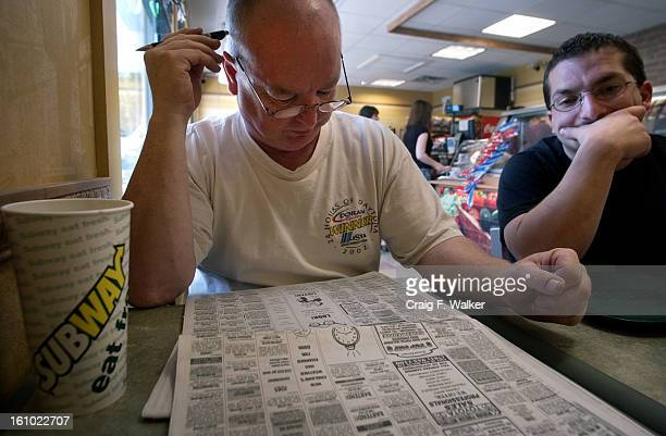 JULY 19 2004 Alan McWilliams looks through the classified ads of the Boston Globe while having lunch with his son Erik a Subway where Alan works as a...