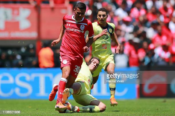 Alan Medina of Toluca struggles for the ball with Mateus Uribe of America during the 15th round match between Toluca and America as part of the...