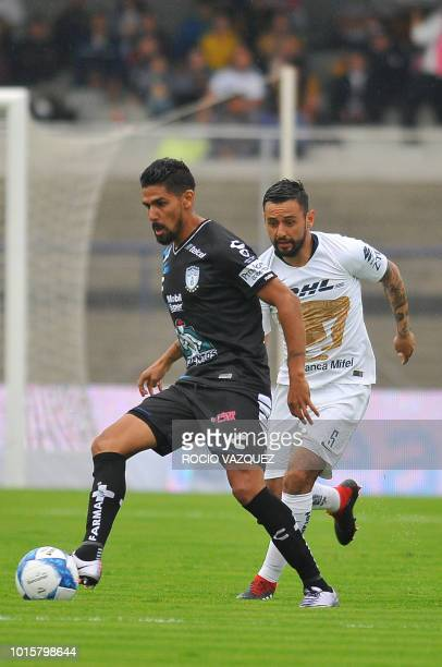 Alan Mendoza of Pumas vies for the ball with Franco Jara of Pachuca during their Mexican Apertura tournament football match at the Olimpico...