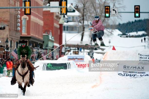 Alan Mikkelson races down Harrison Avenue while skier Jason Dahl airs out off the first jump of the Leadville ski joring course during the 71st...