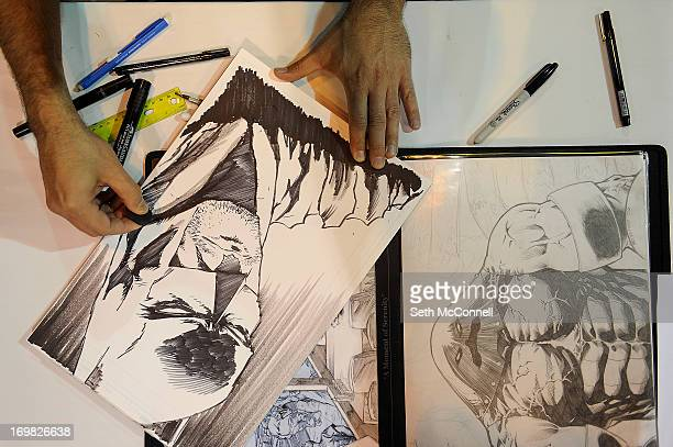 Alan Moorefield sketches an image of Batman while seated at his booth during Denver Comic Con at the Colorado Convention Center on June 2 2013 in...