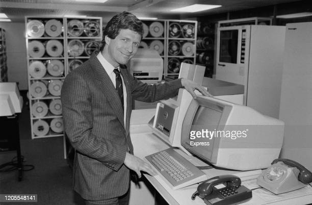 Alan Moss poses beside a monitor with racks of magnetic tape data storage reels in the background 20th May 1985