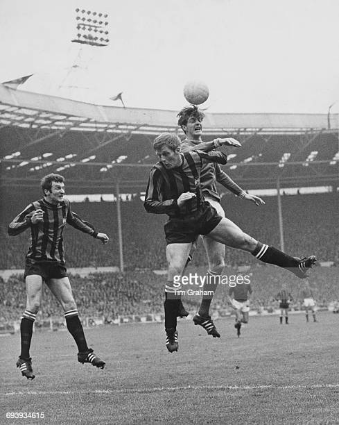 Alan Oakes of Manchester City challenges Allan Clarke of Leicester City for the ball in the air as Neil Young of Manchester City looks on during...
