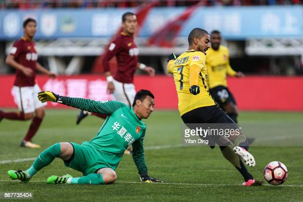 Alan of Guangzhou Evergrande takes a shot against Yang Cheng of Hebei China Fortune during the Chinese Super League match between Hebei China Fortune...