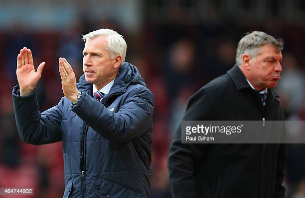 Alan Pardew manager of Crystal Palace celebrates victory as Sam Allardyce manager West Ham United look dejected after the Barclays Premier League...
