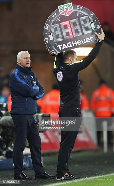 Alan Pardew Manager of Crystal Palace watches the fourth official indicating seven minutes of extra time during the Premier League match between...