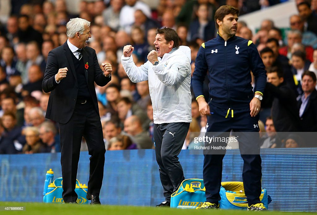 Alan Pardew manager of Newcastle United celebrates with his assistant John Carver next to Mauricio Pochettino, manager of Spurs at the final whistle of the Barclays Premier League match between Tottenham Hotspur and Newcastle United at White Hart Lane on October 26, 2014 in London, England.