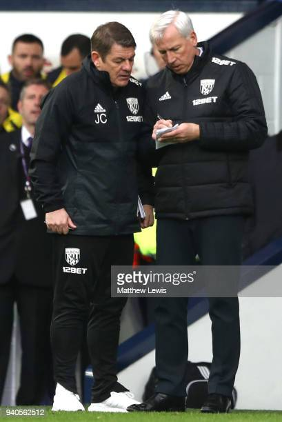 Alan Pardew Manager of West Bromwich Albion makes notes with John Carver during the Premier League match between West Bromwich Albion and Burnley at...