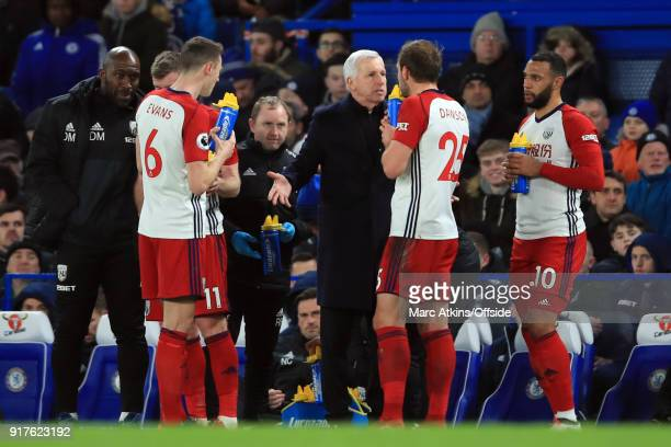 Alan Pardew manager of West Bromwich Albion shrugs his shoulders as he speaks to Craig Dawson during the Premier League match between Chelsea and...