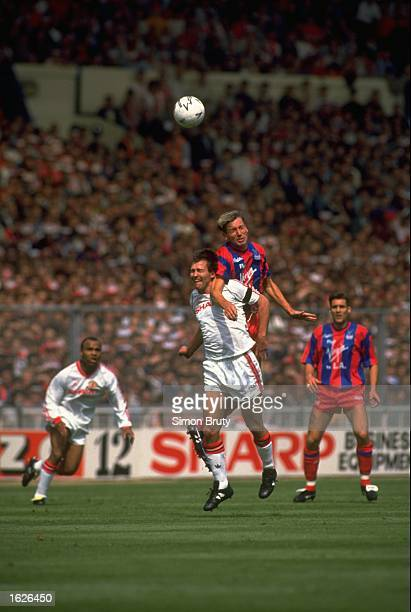 Alan Pardew of Crystal Palace out jumps Bryan Robson of Manchester United during the FA Cup final at Wembley Stadium in London The match ended in a...