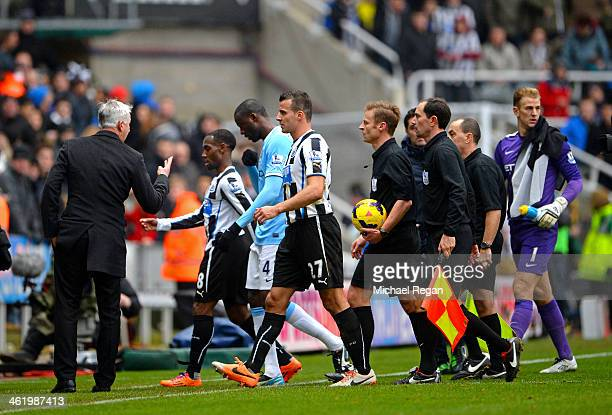 Alan Pardew the Newcastle manager complains to Referee Mike Jones and his officials as they leave the pitch at half time during the Barclays Premier...