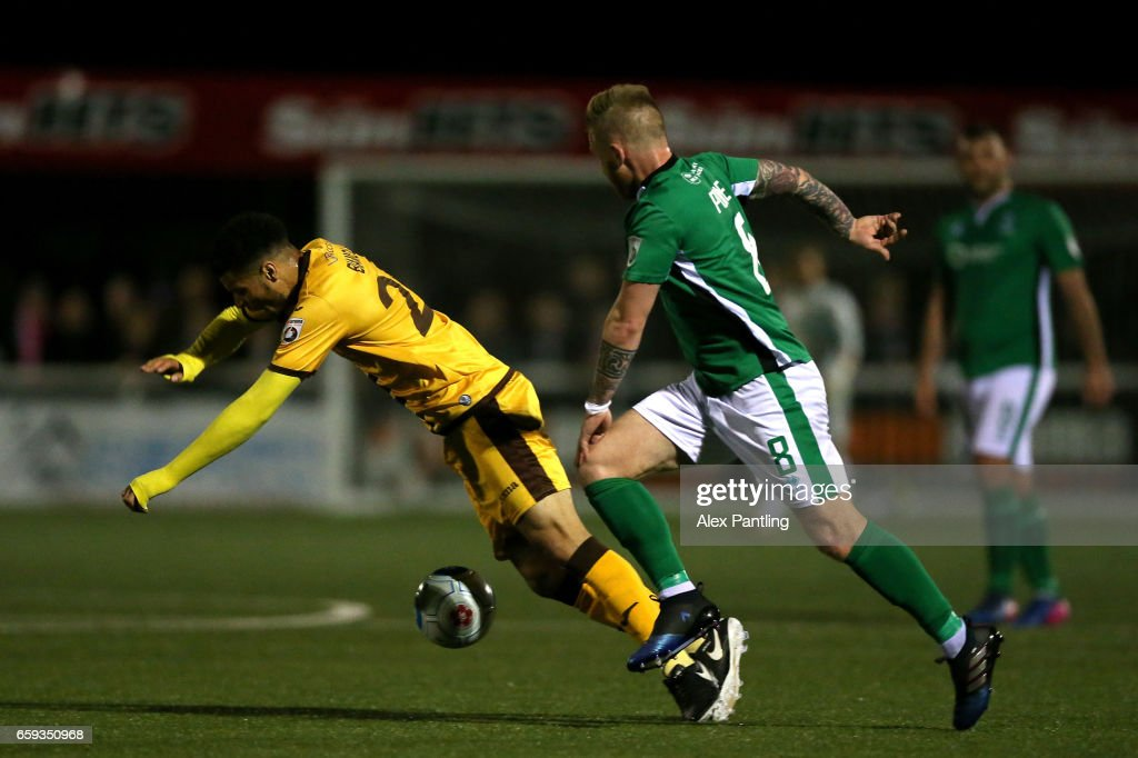Alan Power of Lincoln City tackles Maxime Biamou during the Vanarama National League match between Sutton United and Lincoln City at Gander Green Lane on March 28, 2017 in Sutton, Greater London.