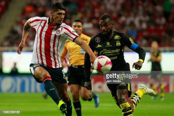 Alan Pulido of Chivas and Gabriel Achilier of Morelia fight for the ball during a 14th round match between Chivas and Morelia as part of Torneo...